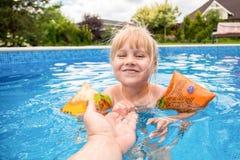 Милый белокурый ребёнок плавает на бассейне swimmig с водой покрашенной синью outdoors, улыбками и рукой ` s владением родительск Стоковое фото RF