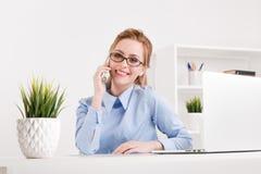 Милый белокурый телефон девушки офиса говоря на ее рабочем месте стоковые изображения