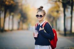 Милый битник предназначенный для подростков с красной сумкой выпивает milkshake от улицы пластичной чашки идя между зданиями Мила стоковое изображение rf