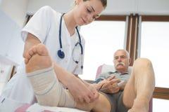 Милый врач перевязывая старейшины укомплектовывает личным составом сломанную ногу Стоковая Фотография RF