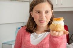 Милый девочка-подросток показывая сладкую выпечку стоковое фото rf