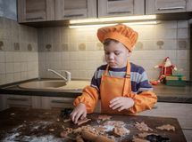 Милый европейский мальчик в костюме повара делает печенья имбиря стоковые изображения rf