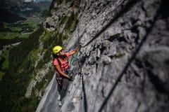 Милый, женский альпинист на a через ferrata стоковая фотография