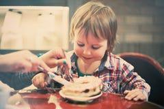 Милый жизнерадостный белокурый мальчик сидя в кафе с куском пирога Стоковая Фотография RF