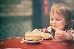 Милый жизнерадостный белокурый мальчик сидя в кафе с куском пирога Стоковое Изображение RF