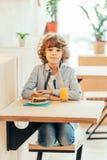 милый жизнерадостный курчавый мальчик сидя в кафе в кафе с куском пирога Стоковое Изображение RF