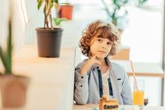 милый жизнерадостный курчавый мальчик сидя в кафе в кафе с куском пирога Стоковое фото RF