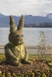 Милый зайчик пасхи от соломы сидит в flowerbed Стоковые Фото