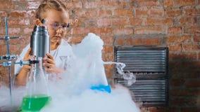 Милый исследователь ребенка проводит эксперимент с жидким азотом стоковое изображение