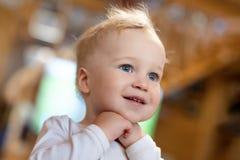 Милый кавказский белокурый мальчик малыша приятно удивил смотреть где-то внутри помещения Прелестный маленький ребенок держа руки стоковая фотография rf