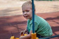 Милый кавказский белокурый ребенок с голубыми глазами сидит на крышке игровой площадки с игрушкой, желтого экскаватора Смешной вз стоковое фото