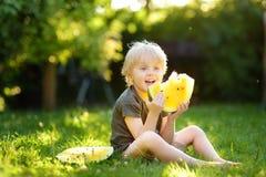 Милый кавказский мальчик со светлыми волосами есть желтый арбуз outdoors стоковые изображения