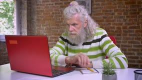 Милый кавказский старик сидит рядом с его компьютером и пишет примечания, белые волосы и бороду, случайный и холодок акции видеоматериалы