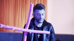 Милый кавказский человек в кожаной куртке поет и танцует на софе держа розовый крест сток-видео