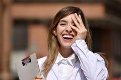 Милый колумбийский женский доктор Laughing Wearing Лаборатория Пальто с доской сзажимом для бумаги стоковая фотография