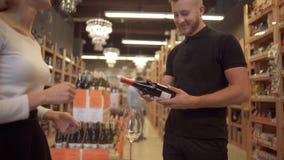 Милый коротк-с волосами продавец девушки предлагает вино к посетителю Мужской покупатель принимает бутылку вина предложенную прод акции видеоматериалы