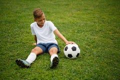 Милый, красивый парень при футбольный мяч сидя на предпосылке зеленой травы Футболист на стадионе Стоковая Фотография