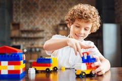 Милый курчавый с волосами мальчик строя его автомобиль мечты Стоковая Фотография