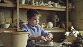 Милый любознательный ребенок делает глиняный горшок на закручивая бросать катит внутри профессиональную мастерскую Керамические в акции видеоматериалы