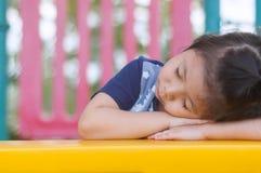Милый маленькая азиатская девушка спать в спортивной площадке стоковое изображение
