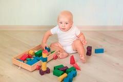 Милый маленький младенец играя с покрашенными деревянными блоками стоковое изображение