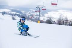 Милый маленький ребенок дошкольного возраста в синем пиджаке, катаясь на лыжах счастливо на a Стоковая Фотография