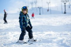 Милый маленький ребенок дошкольного возраста в синем пиджаке, катаясь на лыжах счастливо на a Стоковое Фото