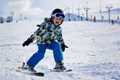 Милый маленький ребенок дошкольного возраста в синем пиджаке, катаясь на лыжах счастливо на a Стоковое фото RF