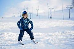 Милый маленький ребенок дошкольного возраста в синем пиджаке, катаясь на лыжах счастливо на a Стоковая Фотография RF