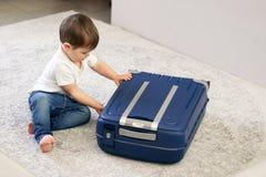 Милый маленький ребенок закрывая голубой чемодан закончил упаковать на каникулы стоковое изображение rf