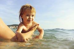 Милый маленький ребенок плавает в воде стоковые фотографии rf