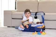 Милый маленький ребенок со смешным выражением стороны сидя в голубой соломенной шляпе удерживания чемодана в руках, упакованных н стоковое фото rf