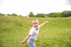 Милый маленький ребёнок сидит в траве стоковое изображение rf