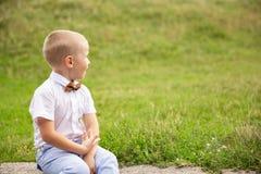 Милый маленький ребёнок сидит в траве стоковое фото