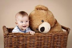 Милый маленький ребёнок сидя в плетеной корзине с большим плюшевым медвежонком плюша Стоковое фото RF
