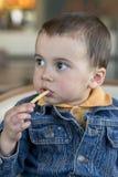 Милый маленький ребёнок сидя на кафе есть вкусных французов жарит европейско стоковая фотография rf