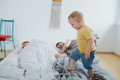 Милый маленький сын пробуя проспать вверх по его родителям стоковые изображения