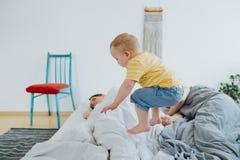Милый маленький сын пробуя проспать вверх по его родителям стоковое изображение