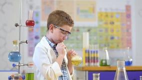 Милый маленький ученый делает эксперимент по лаборатории с жидкостью сток-видео