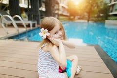Милый малый человеческий ребенк девушки сидя близко к цветку бассейна нося на солнечный день Стоковое Фото