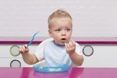 Милый малыш в голубом bib есть банан в современной кухне Стоковая Фотография