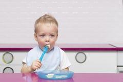 Милый малыш в голубом bib есть банан в современной кухне Стоковое фото RF