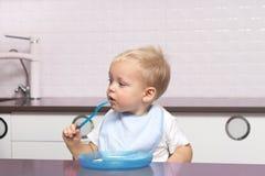 Милый малыш в голубом bib есть банан в современной кухне Стоковое Изображение RF