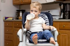Милый малыш в childchair в кухне в питьевом молоке традиционного стиля от бутылки стоковые фото