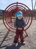 Милый малыш маленькой девочки стоя на конструкции спортивной площадки близко взбираясь Стоковое Изображение RF