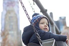Милый малыш на качании на спортивной площадке против небоскребов NY Съемка весны или осени Стоковое Изображение