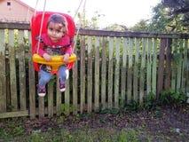 Милый малыш отбрасывая в ее задворк перед старой загородкой Стоковое фото RF