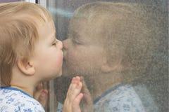 Милый малыш полагаясь к окну и целуя его отражение в mirrow Стоковые Фото