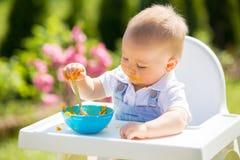 Милый малыш с грязной стороной есть обед в саде, сидя внутри Стоковые Изображения RF