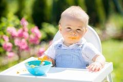 Милый малыш с грязной стороной есть обед в саде, сидя внутри Стоковые Фото